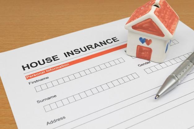 Formulaire de demande d'assurance habitation avec maison modèle et stylo