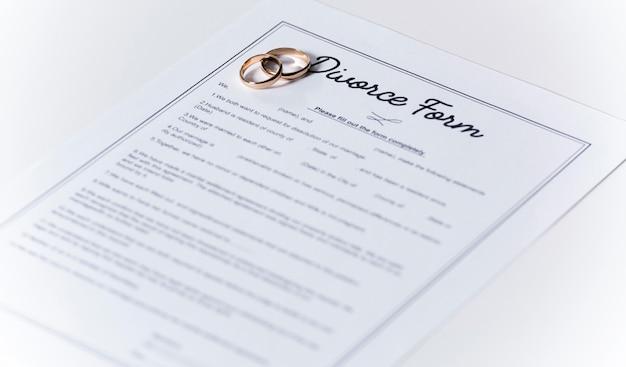 Formulaire de divorce avec anneaux de mariage sur la table