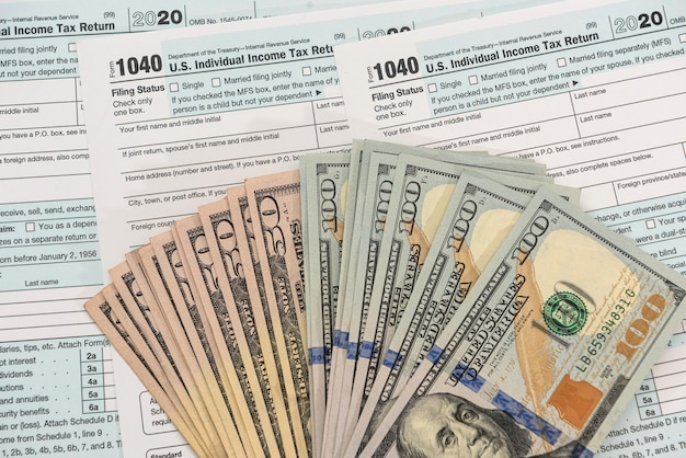 Formulaire fiscal 1040 avec nous billets de 100 dollars, concept de comptable économique