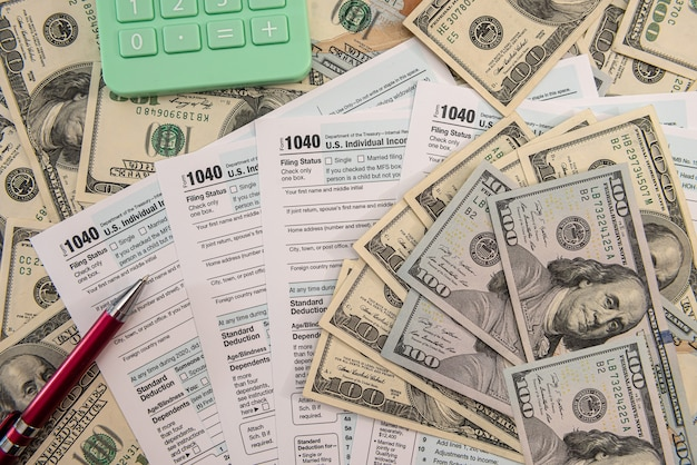 Formulaire fiscal 1040 avec stylo et billets en dollars américains, concept financier