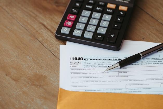 Formulaire d'impôt américain sur le revenu des particuliers et calculatrice sur un bureau en bois.