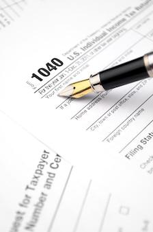Formulaire d'impôt en cours de remplissage avec un ancien stylo-plume