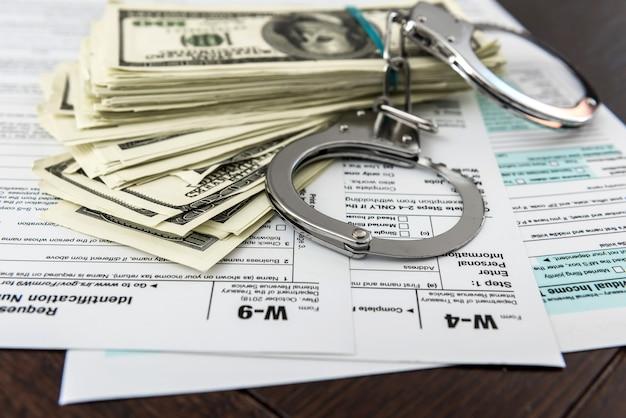 Formulaire d'impôt sur le dollar et les menottes de temps de crime illégal au bureau