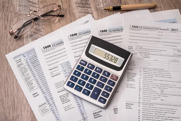 Formulaire d'impôt individuel 1040 avec stylo et calculatrice