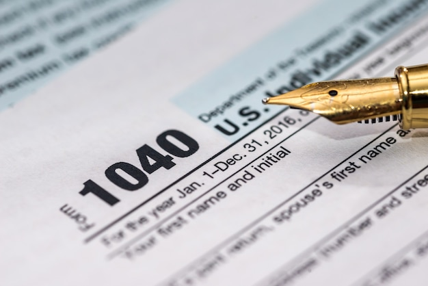 Formulaire d'impôt individuel 1040 avec stylo sur table en bois
