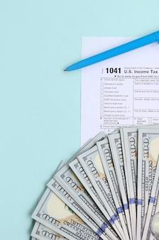 Formulaire d'impôt se trouve près de cent dollars et stylo bleu sur