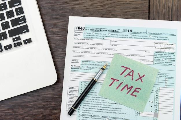 Formulaire d'impôt sur le temps financier avec ordinateur portable et calculatrice. documents de bureau. comptabilité