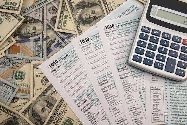 Formulaire individuel américain 1040 avec calculatrice de billets d'un dollar et papiers au stylo. notion de comptabilité