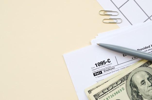 Formulaire irs 1095-c l'offre d'assurance maladie fournie par l'employeur et la couverture fiscale en blanc se trouvent avec un stylo et plusieurs centaines de dollars sur la page du calendrier