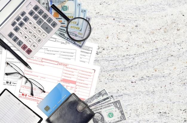 Le formulaire irs w-2 sur les salaires et les impôts se trouve sur une table de bureau plate et prêt à être rempli