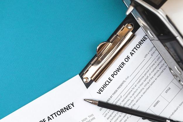 Formulaire de procuration de véhicule. bureau et presse-papiers avec accord. photo vue de dessus