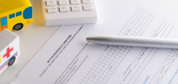 Formulaire de réclamation d'assurance automobile avec modèle de voiture et stylo