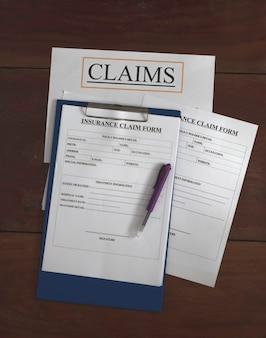 Formulaire de réclamation d'assurance mis sur planche de bois, lumière floue autour