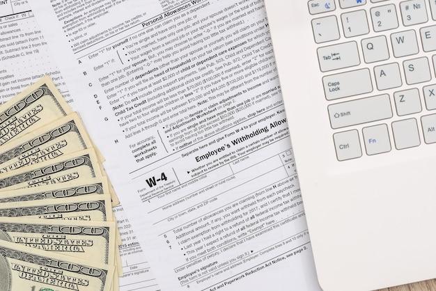 Formulaire w-4 avec argent et ordinateur personnel