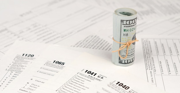 Les formulaires fiscaux sont près des rouleaux de cent dollars