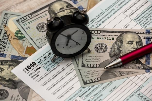 Formulaires d'impôt 1040 avec stylo-horloge et billets d'un dollar