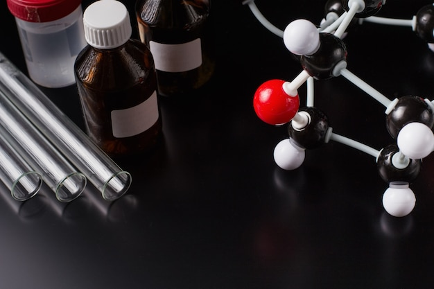 Formule moléculaire et équipement de laboratoire sur un fond sombre.