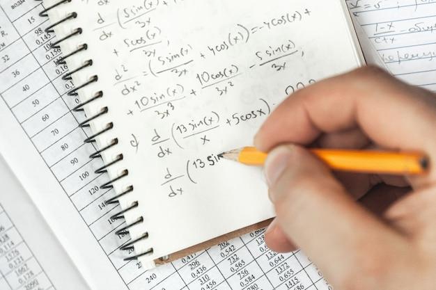 Les formules mathématiques sont écrites au crayon dans un cahier tenant un homme dans les mains, des problèmes de mathématiques
