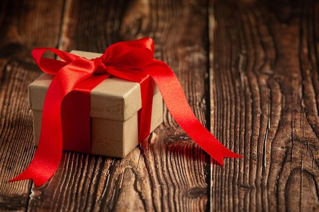 Fort de cadeau avec noeud de ruban rouge sur fond de bois