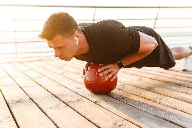 Fort jeune sportif dans les écouteurs, faire des exercices