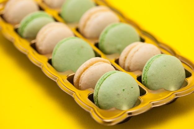 Fort de macarons français colorés frais sur fond jaune. dessert sucré
