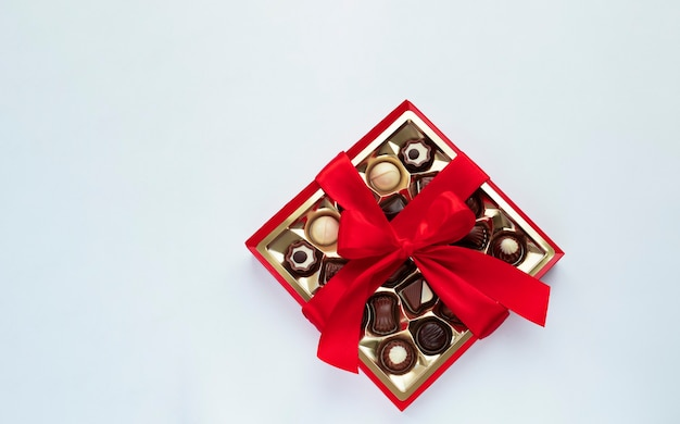 Fort de pralines au chocolat avec noeud rouge sur bleu clair