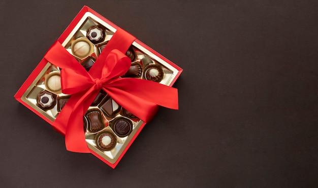 Fort de pralines au chocolat avec noeud rouge sur brun foncé