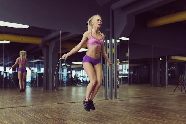 Forte et belle femme athlétique s'entraînant dans la salle de gym