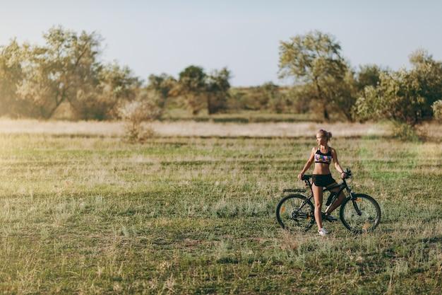 La forte femme blonde en costume coloré est assise sur un vélo dans une zone désertique avec des arbres et de l'herbe verte et regarde le soleil. notion de remise en forme.
