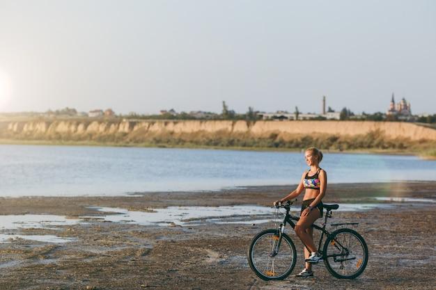 La forte femme blonde en costume coloré est assise sur un vélo dans une zone désertique près de l'eau et regarde le soleil. notion de remise en forme.
