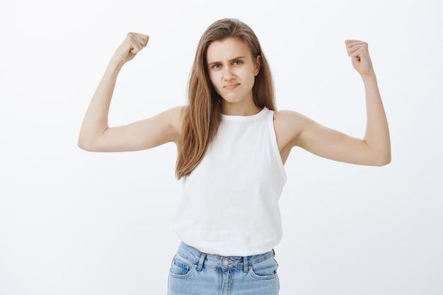 Forte fille blonde impertinente montrant les biceps, les muscles flexibles, l'entraînement en salle de gym, se sentir habilité