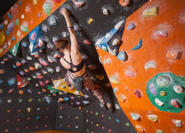 Forte grimpeuse femelle sur un mur d'escalade de rocher intérieur atteint le sommet
