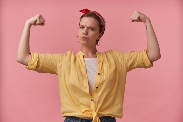 Forte jeune femme athlétique en chemise jaune avec bandeau sur la tête debout et montrant les muscles du biceps à deux mains sur le mur rose