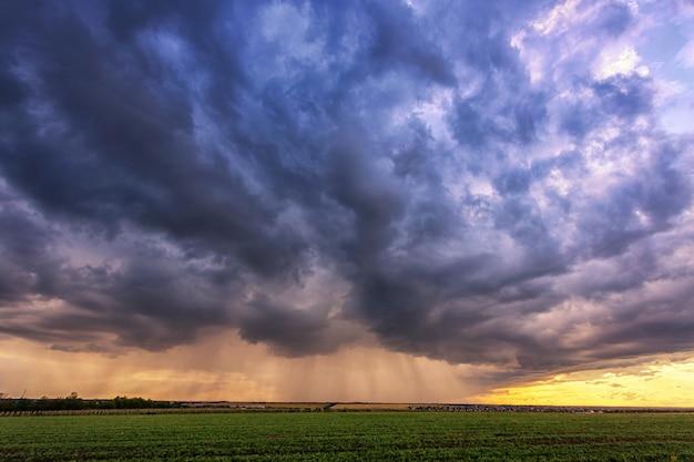 Forte pluie sur un champ avec de beaux nuages d'orage