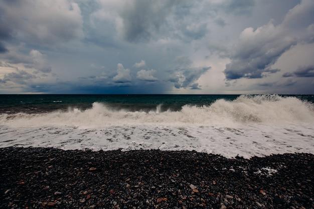 Forte tempête de mer. des vagues blanches roulent sur une plage de galets. cumulus dans le ciel.
