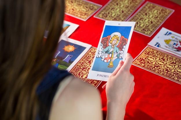 Fortune caissier en utilisant des cartes de tarot sur la table rouge