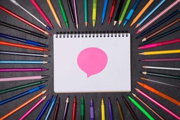 Forum à l'école concept artisanal artisanal. en haut au-dessus de la vue aérienne photo de stylos et crayons colorés autour d'un cahier vierge avec un autocollant à bulles rose isolé sur un tableau noir