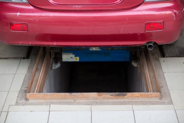 Fosse d'inspection dans le garage et voiture rouge