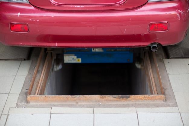 Fosse d'inspection dans le garage et voiture rouge.