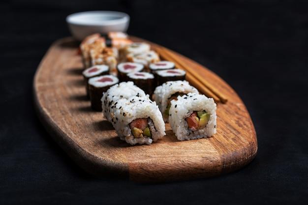 Foto de stock de composición de sushi con maki, california roll y nigiri con palillos y salsa de soja sobre tabla de madera.