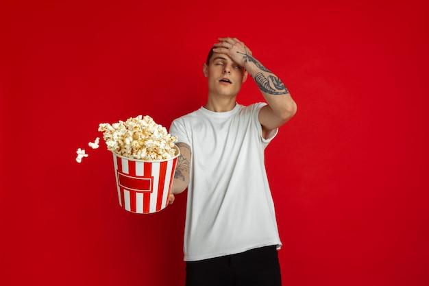 Fou choqué, bouleversé. portrait de jeune homme caucasien sur mur rouge. beau modèle masculin avec pop-corn. concept d'émotions humaines, d'expression faciale, de cinéma et de divertissement.