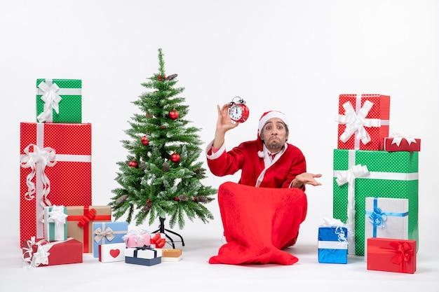 Fou émotionnel surpris confus père noël assis sur le sol et montrant horloge près de cadeaux et arbre de noël décoré sur fond blanc
