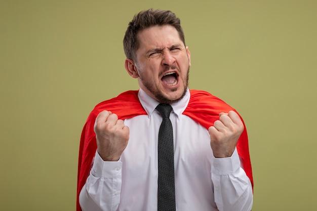 Fou fou et en colère homme d'affaires de super-héros en cape rouge serrant les poings avec une expression agressive va crier sauvage debout sur le mur vert