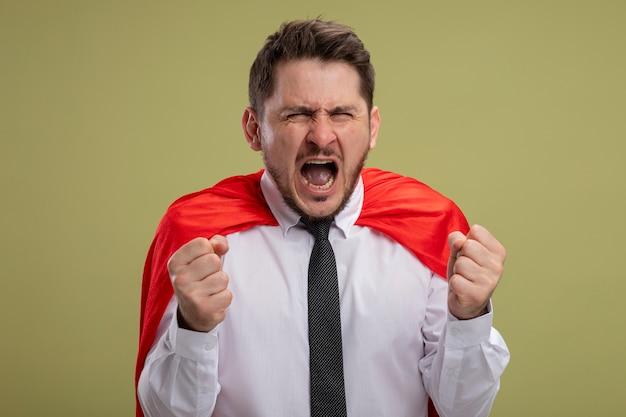 Fou fou et en colère homme d'affaires de super-héros en cape rouge serrant les poings avec une expression agressive va crier sauvage sur mur vert