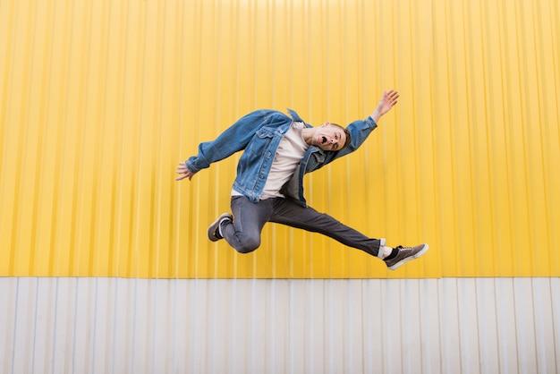 Fou, jeune homme, dans, jean, veste, sauter, contre, fond, de, mur jaune