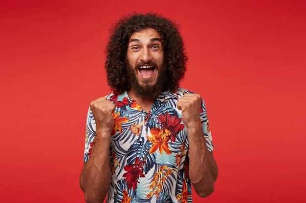Fou de joie attrayant jeune homme barbu brune en chemise à fleurs levant les poings joyeusement et regardant gaiement à la caméra avec de grands yeux et la bouche ouverte, isolé sur fond rouge