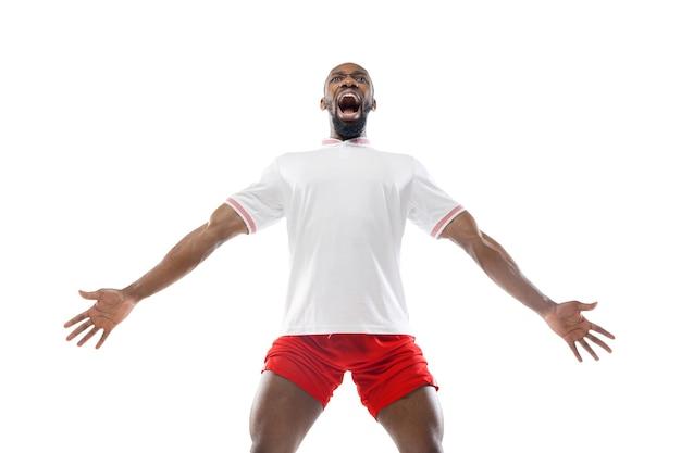 Fou de joie, criant. émotions drôles du football professionnel, joueur de football isolé sur le mur blanc du studio.