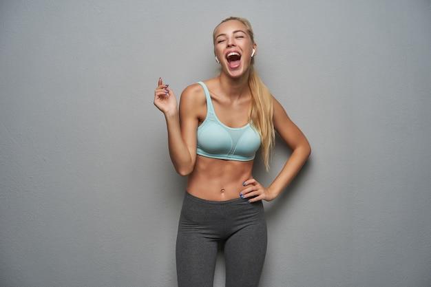 Fou de joie jolie femme blonde sportive avec une coiffure en queue de cheval levant la main joyeusement et riant avec la bouche grande ouverte, debout sur fond gris en vêtements de sport