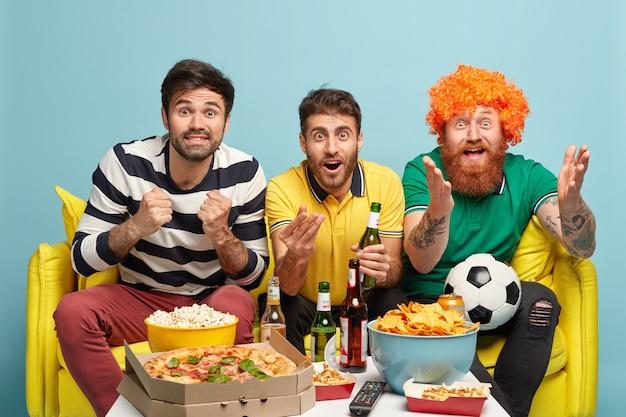 Fou de joie, trois meilleurs amis masculins sont très émotifs, serrent les poings de joie, soutiennent l'équipe de football, regardent le match avec un grand intérêt, s'assoient sur un canapé, posent contre le mur bleu. partisans du sport