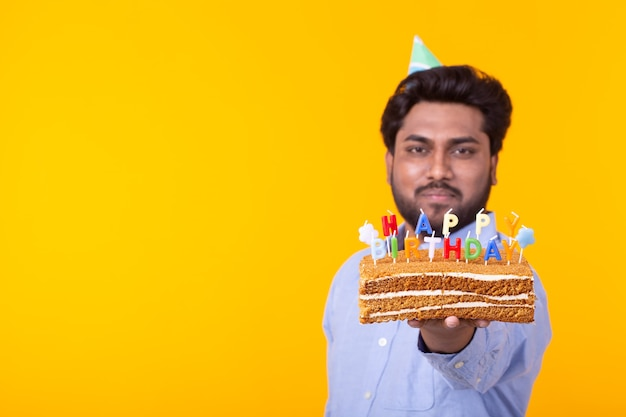Fou joyeux jeune homme indien en papier chapeau de félicitations tenant des gâteaux joyeux anniversaire debout sur